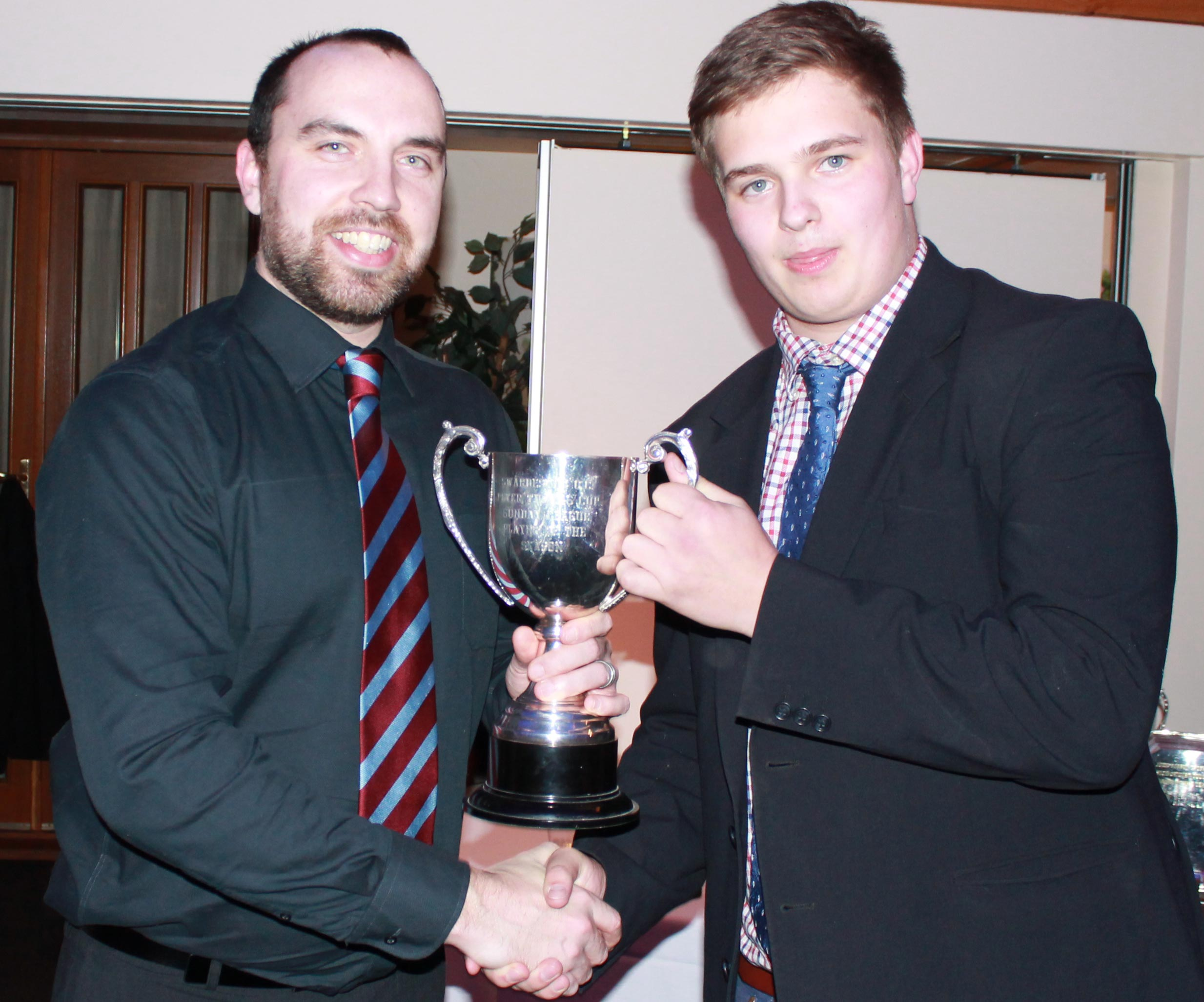 Will Kidner picks up the Peter Thomas Trophy from captain Ben Hogg as Swardeston Sunday player of the year.